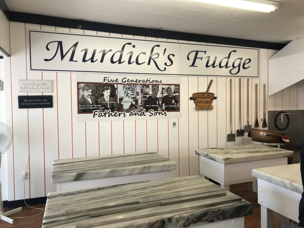 Interior of Murdick's Fudge, several small marble counter tops and signage.