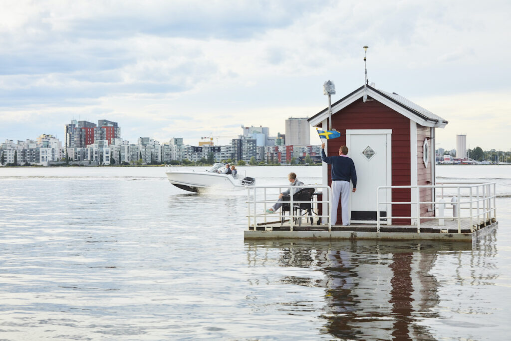 Couple stands on the deck of Utter Inn, Vasteras, Sweden, surrounded by water.