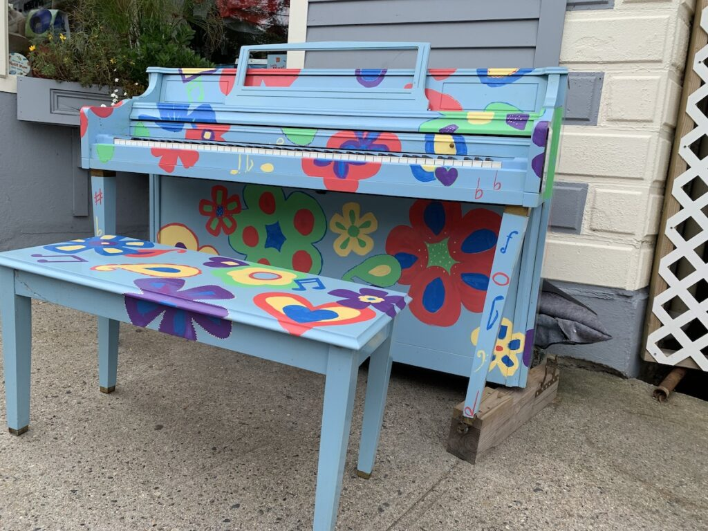 Vibrantly painted wooden piano with bench sets outside.