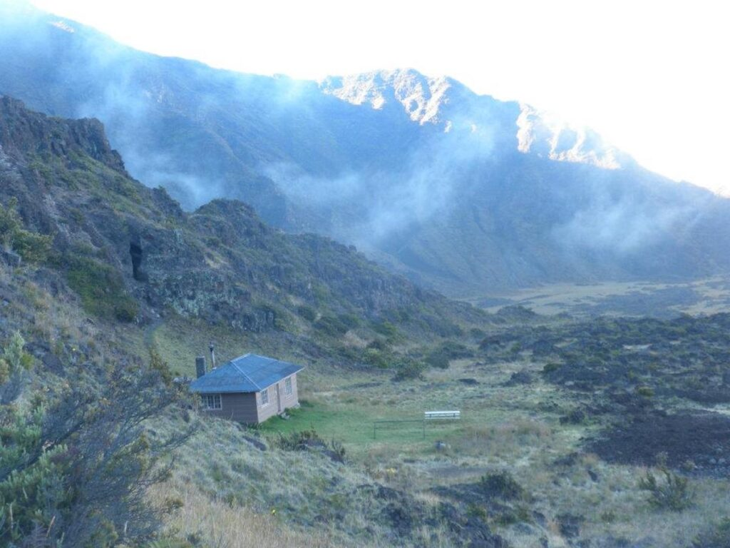 Fog comes through the mountains on a morning at the Hōlua Cabin.