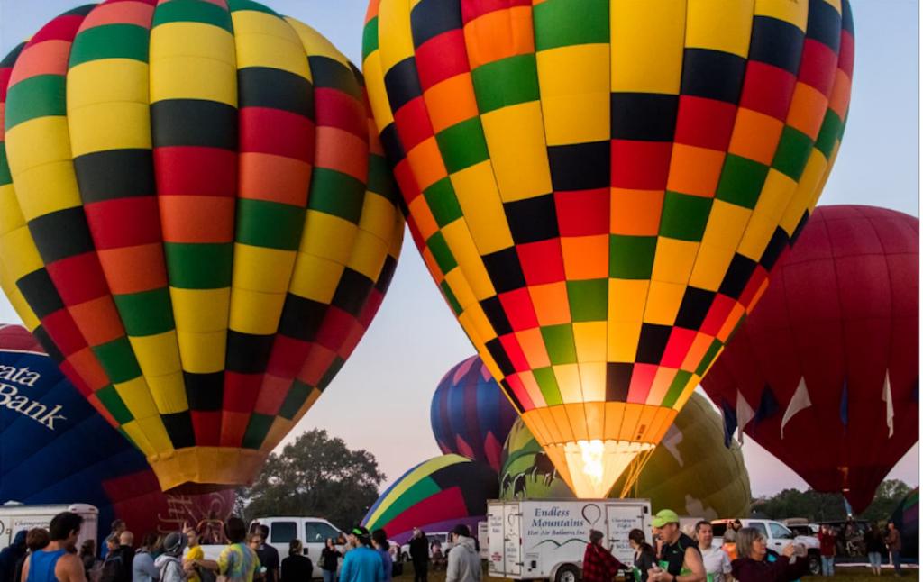 Hot air balloons at dusk still on the ground.