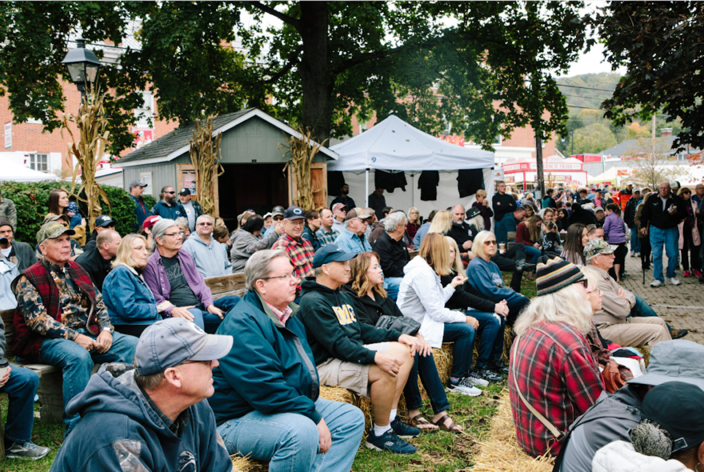 Visitors sit on hay bales at Bedford Fall Foliage Festival.