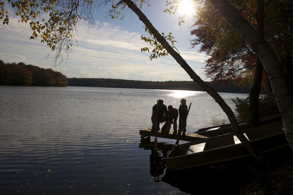 Family boating on a lake in the Pocono Mountains, Pennsylvania.