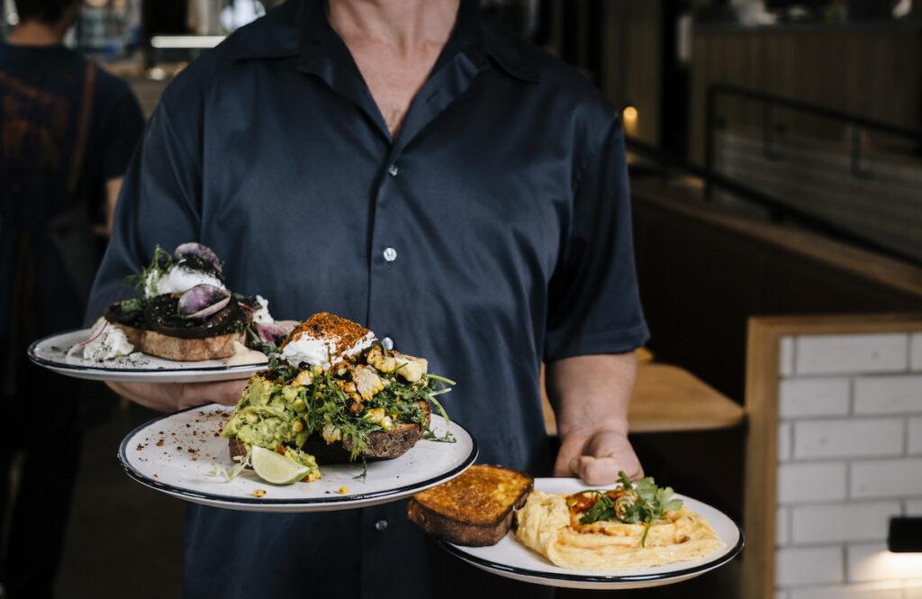Waiter serves food at Melbourne Breakfast, a Rustica Bakery Cafe.