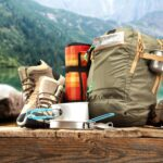 Camping Packing Gear in front of lake and mountains