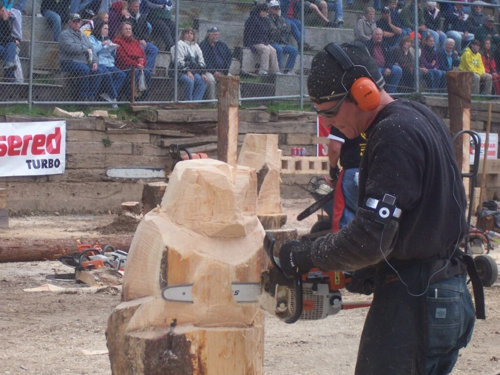 Man carves wood with chainsaw at the Chainsaw Carving Competition in Forksville.
