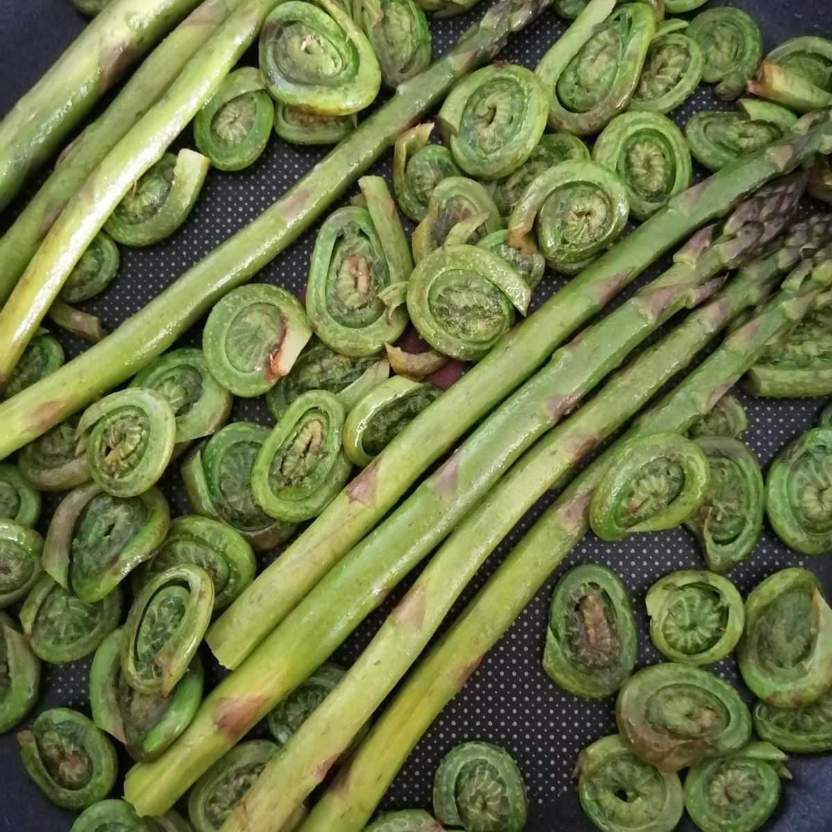 Fried asparagus and fiddleheads on a frying pan close up