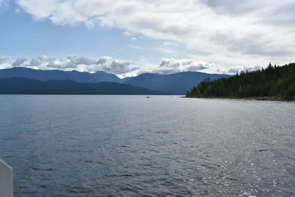 Riding the Balfour Ferry, looking out at the water and mountains and white clouds in the background.