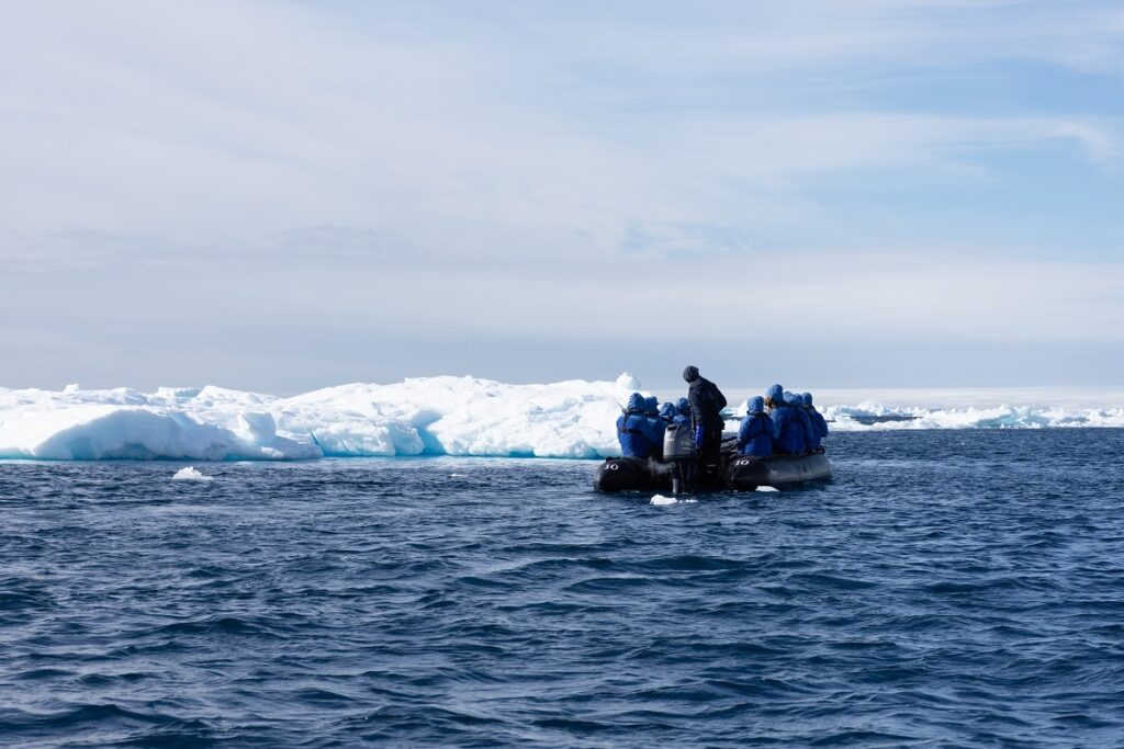 Group of tourists in blue jackets on a zodiac boat touring around icebergs in Antarctica.