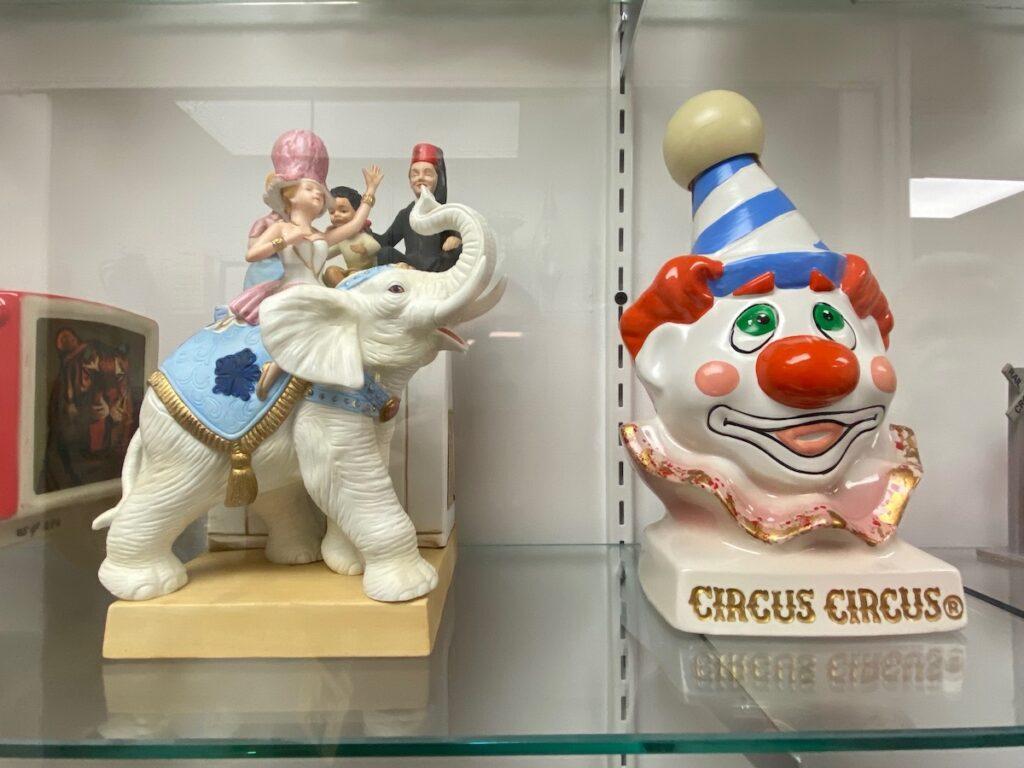 Ceramic clown and circus elephant on display.