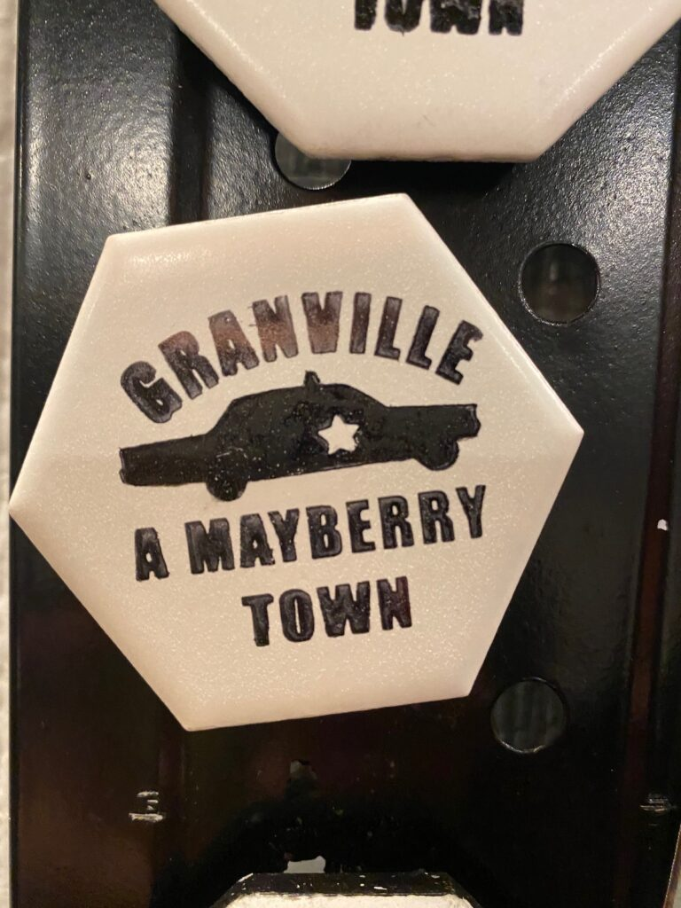 """""""Gainville, A Mayberry Town,"""" button with cop car at center."""