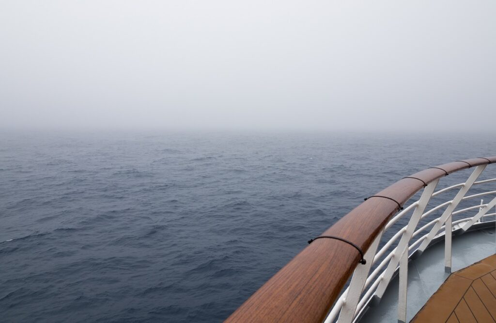 The bow of the ship with wood and metal railing and wooden deck in fairly calm seas with fog ahead. Visibility is limited.