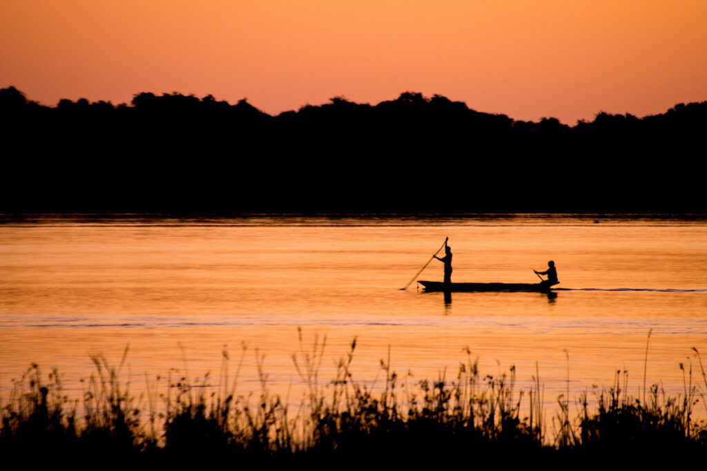 Locals canoeing on the Zambezi River at sunset.