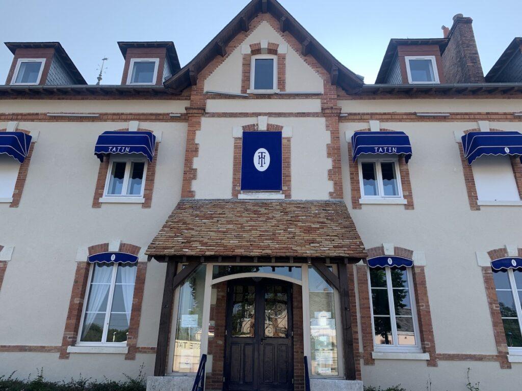 Maison Tatin Hotel with blue awnings.
