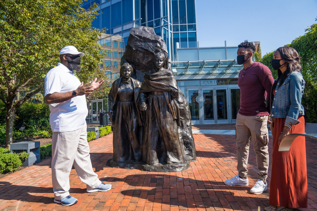 Tourists gathered around a statue in Alexandria, Virginia, photographed by Chris Cruz of Visit Alexandria.