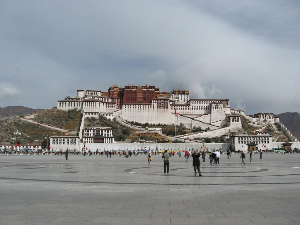 Exterior of the Potala Palace in Lhasa with many tourists walking and observing its large scale.