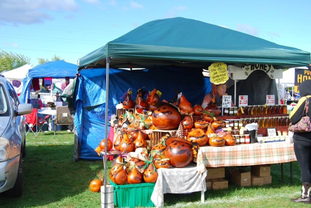 Vendor tent with decorated pumpkins and jars of honey at the 2016 Pennsboro Pumpkin Festival.