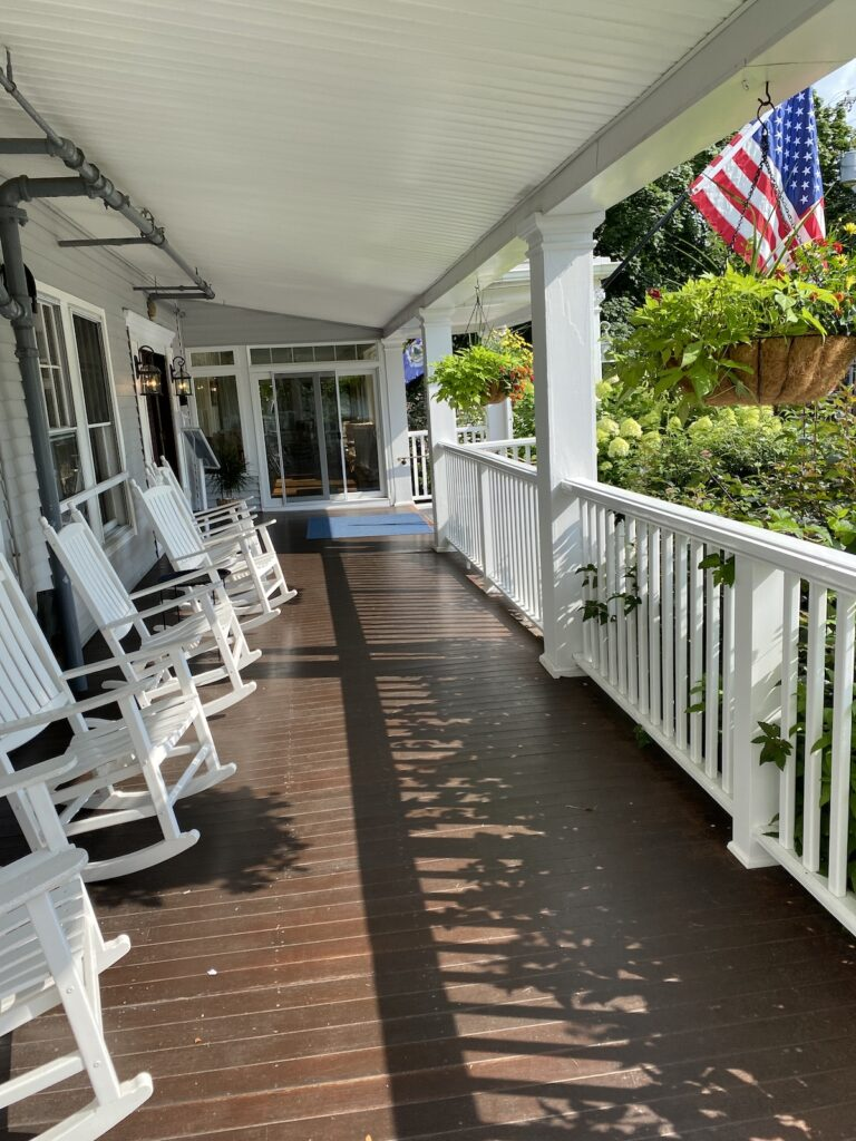 Nonantum porch with white rocking chairs.