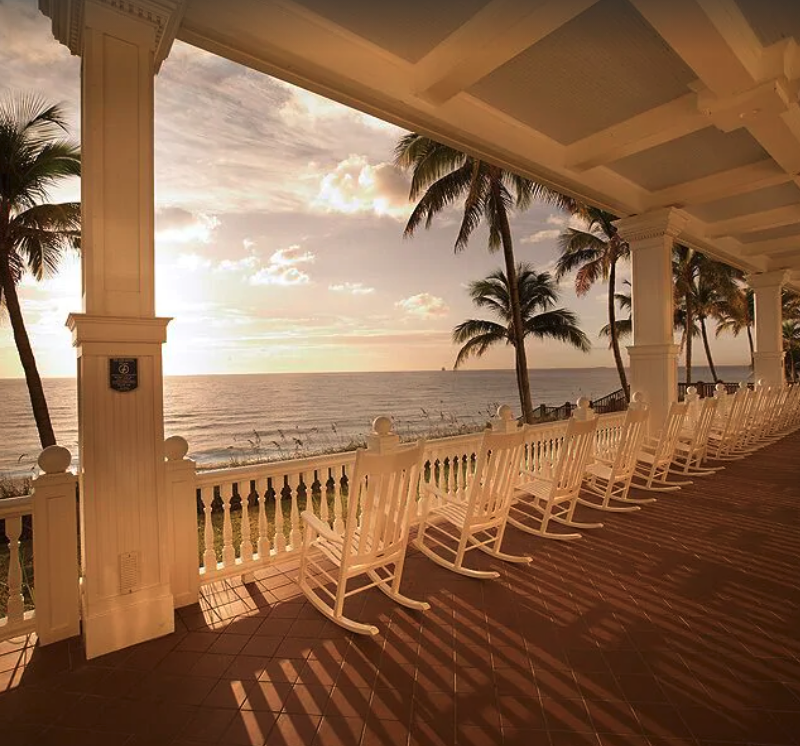row of white rocking chairs looking out over the Atlantic ocean at a condominium in Fort Lauderdale
