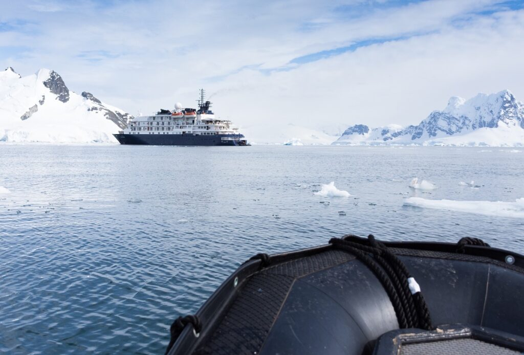 A ship anchored in Paradise Bay Antarctica, photographed from a Zodiak boat. Snow covered mountains surround the bay and small iceberg are seen in the foreground.