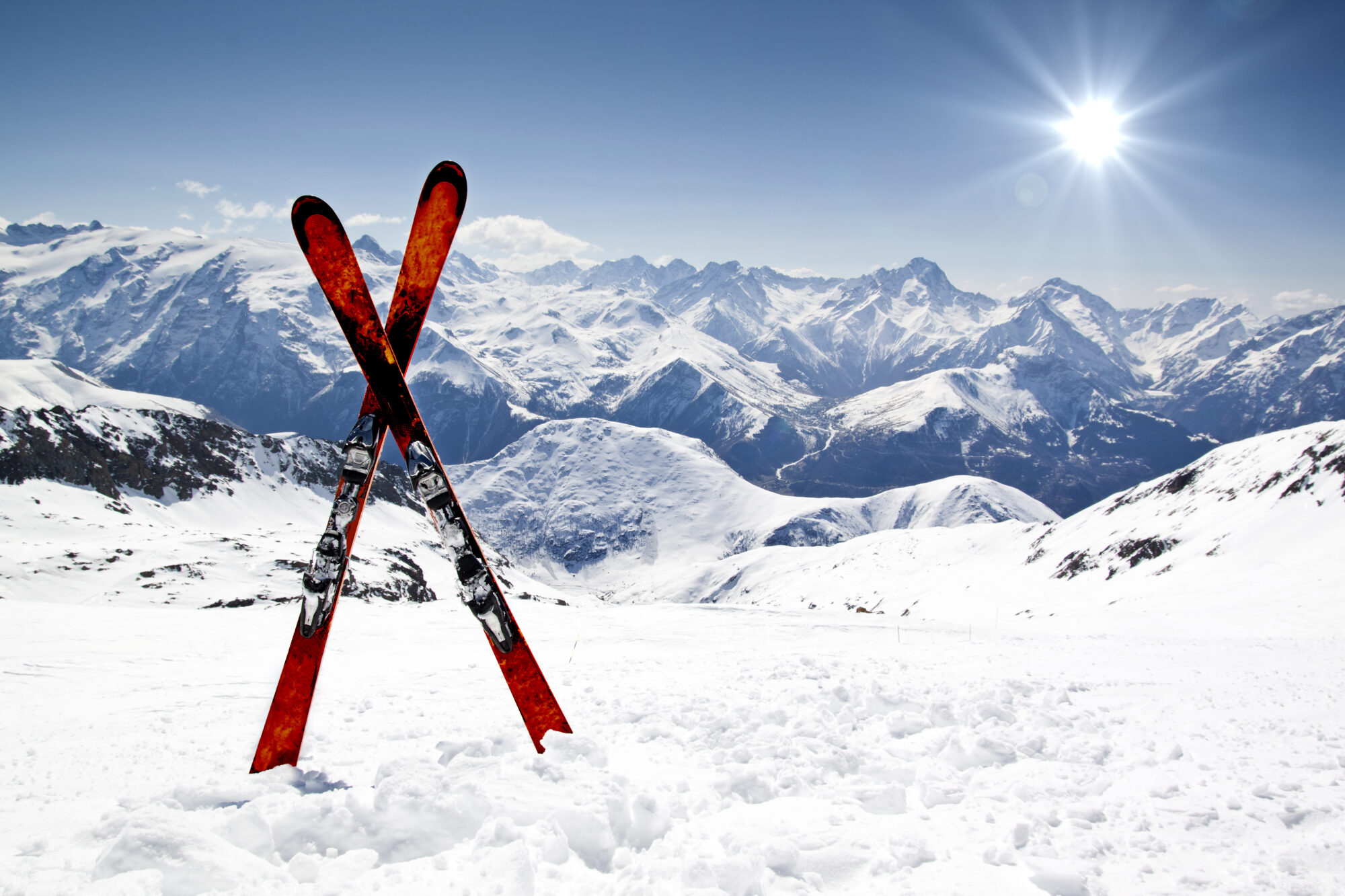 Pair of cross skis in snow in front of mountains