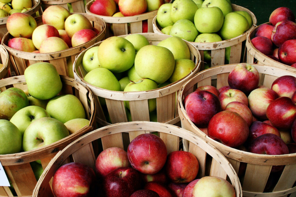 Wooden crates filled with red and green apples.
