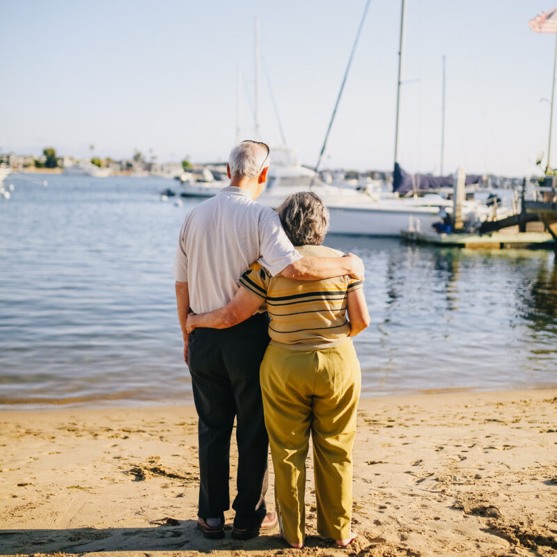Elderly couple standing on the shore