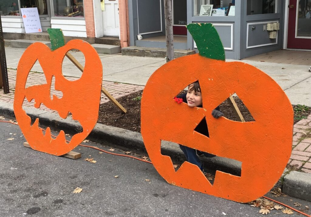Child takes picture in pumpkin sign, with face holes, at the Pumpkin Festival in the Pocono Mountains.