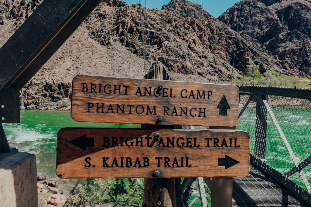 Wooden trail signs on the Bright Angel Bridge by the green Colorado River in the Grand Canyon at Grand Canyon National Park in Arizona.