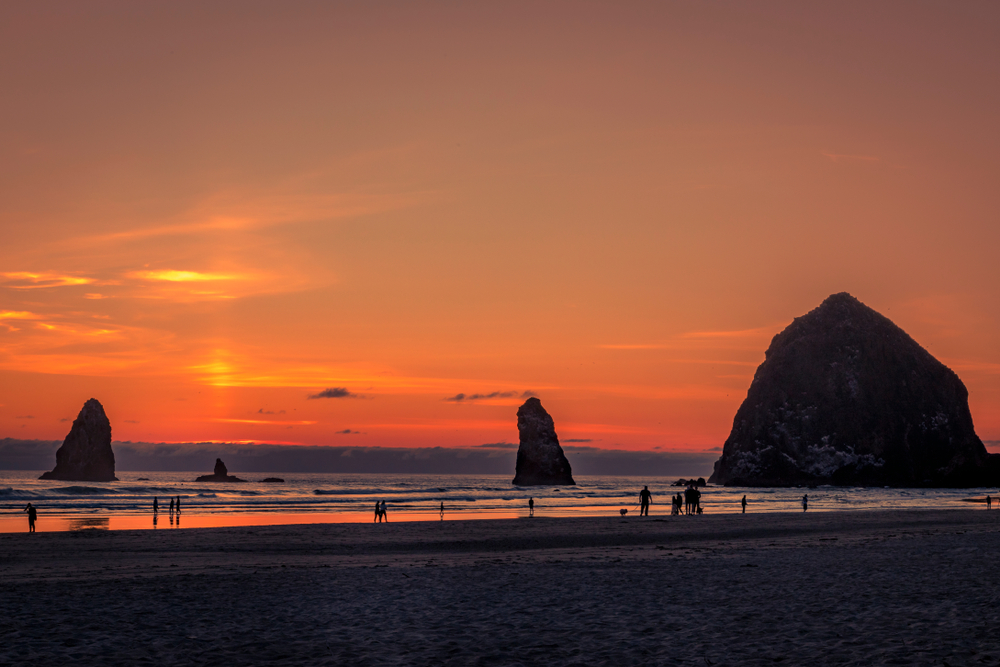 Colorful summer sunset on Cannon Beach Oregon with people and dogs walking on the beach