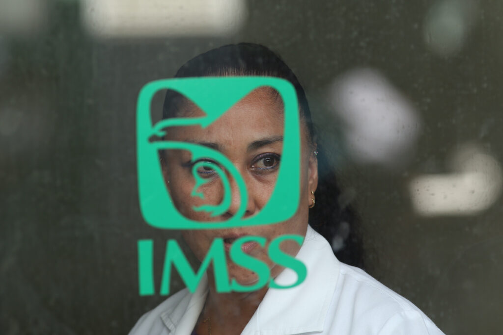 Woman in the local hospital of social security of the community walks passed IMSS emblem in Jamiltepec, Oaxaca Mexico.