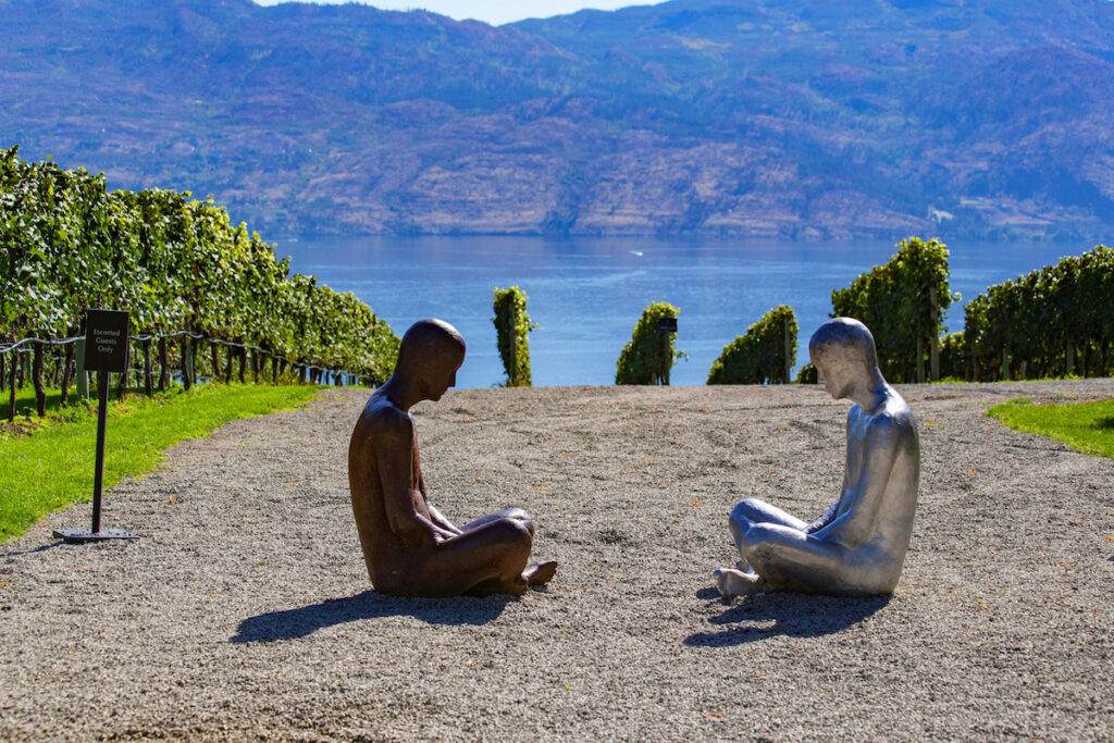 Sculpture of two people sitting across from each other, cross legged and with heads slightly bowing, at Mission Hill Family Estate