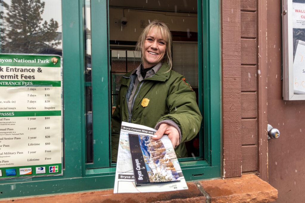 Female blond National Park Ranger hands out brochure through window at Bryce National Park, Utah.