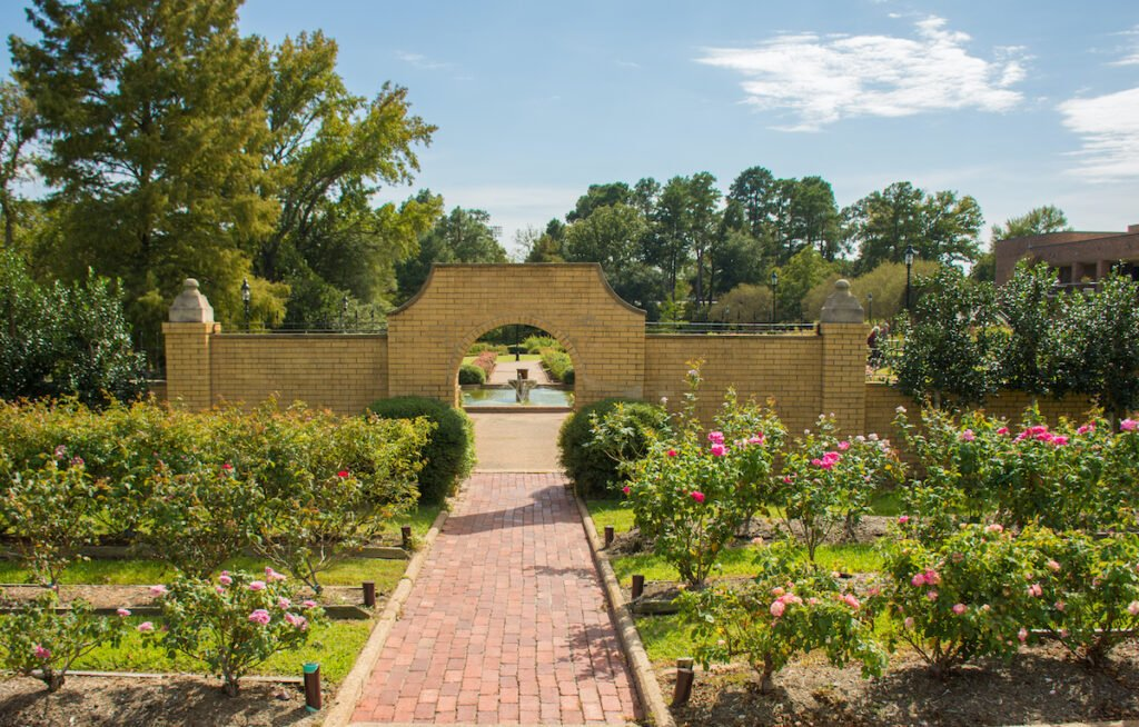 Pathway leading through rose garden with brick archway.