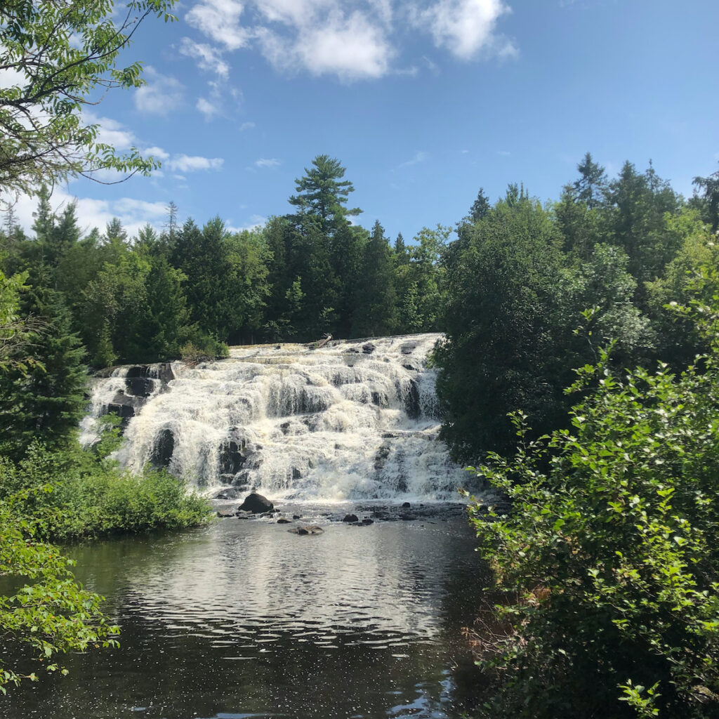 Bond Falls at the Upper Peninsula on a summer day with green foliage surrounding the river banks.