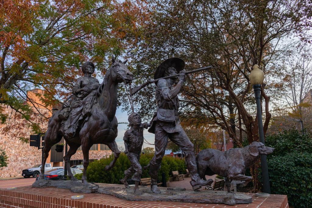 The Gateway statue by Michael Boyett, honoring the first settlers of Texas during fall.