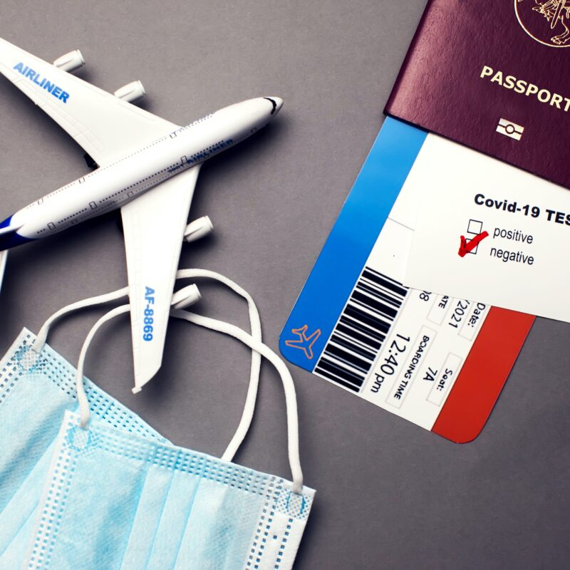 Traveling during COVID-19 pandemic, passport with airline ticket, covid-19 negative test, medical masks and plane on grey background, airport security health and safety check