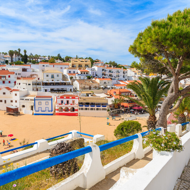 Promenade along street in Carvoeiro fishing village with view of colourful houses on beach, Algarve, Portugal.