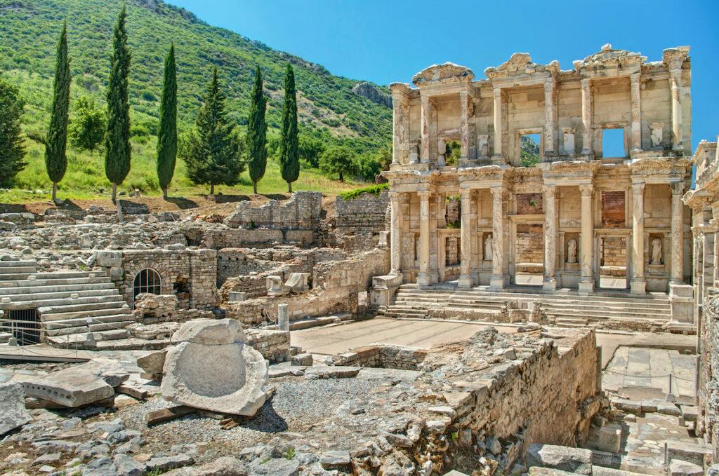Antiche rovine della Biblioteca di Celso a Efeso con cipressi in una giornata di sole in Turchia.