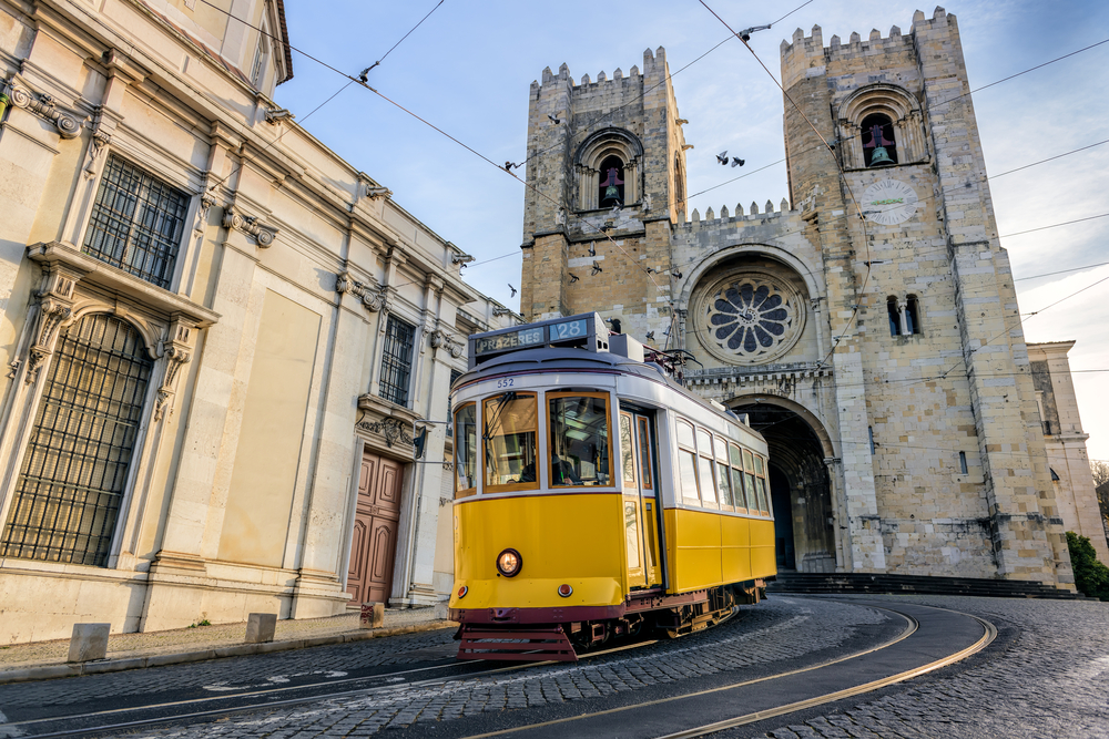 Historic yellow tram 28 passing in front of Santa Maria cathedral in Lisbon, Portugal