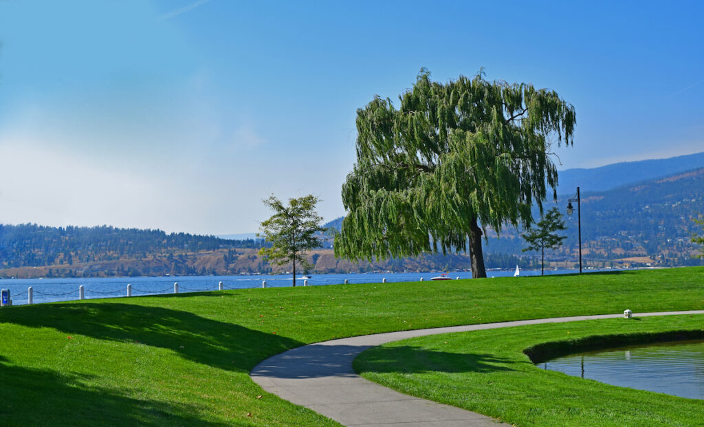 Perfectly manicured green grass and walkway at Waterfront Park with beach in the background.