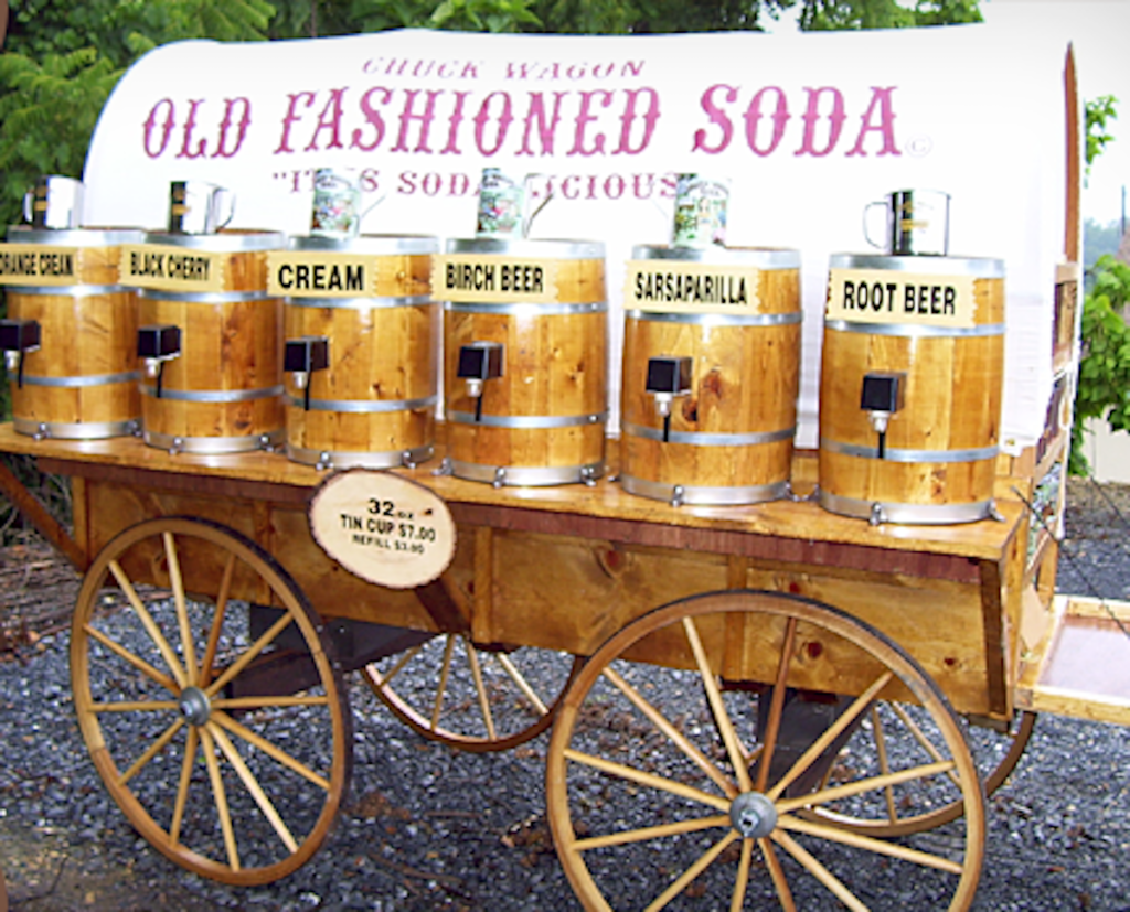 Wooden covered wagon display with barrels of soda on tap for sale.
