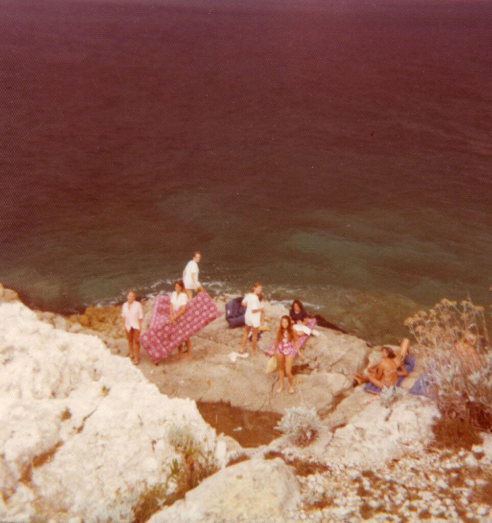 Girls on tour in Pula, Croatia relaxing on the rocks overlooking the sea.