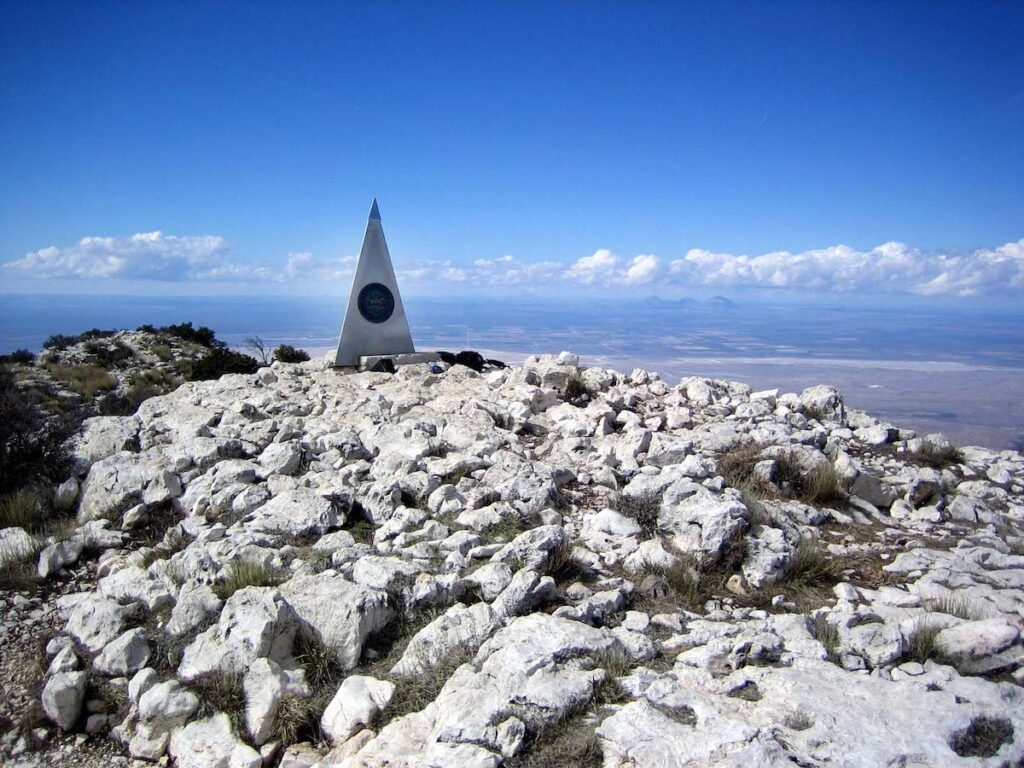 Guadalupe Peak obelisk on a blue sky day, up high with the clouds.