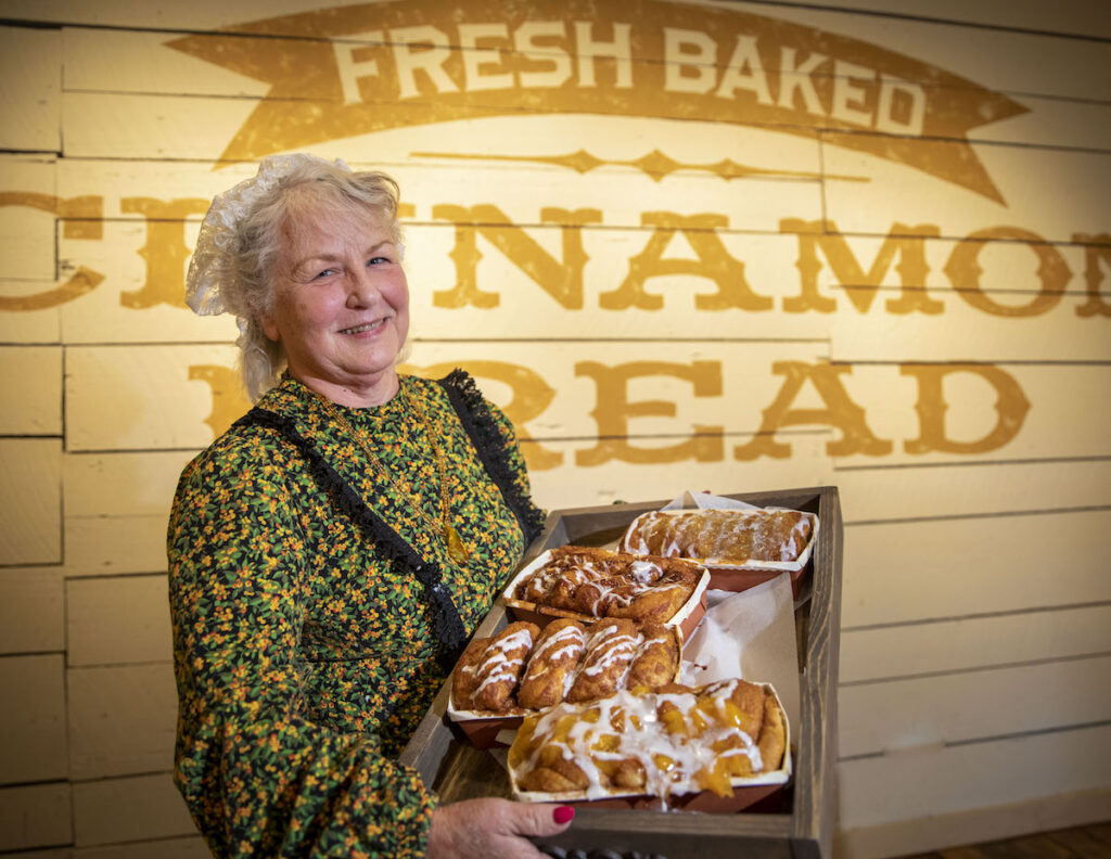 Woman stands holding a pan of Clara Bell's bread at Clara Bell's bakery in Silver Dollar City.