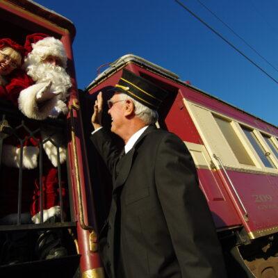 Holiday train conductor high fives santa and mrs. claus