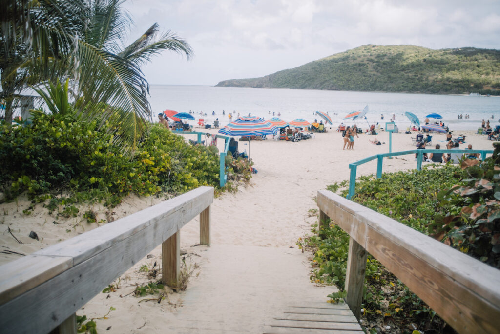 Walkway down to beach, umbrellas and people have fun on the beach and in the ocean.