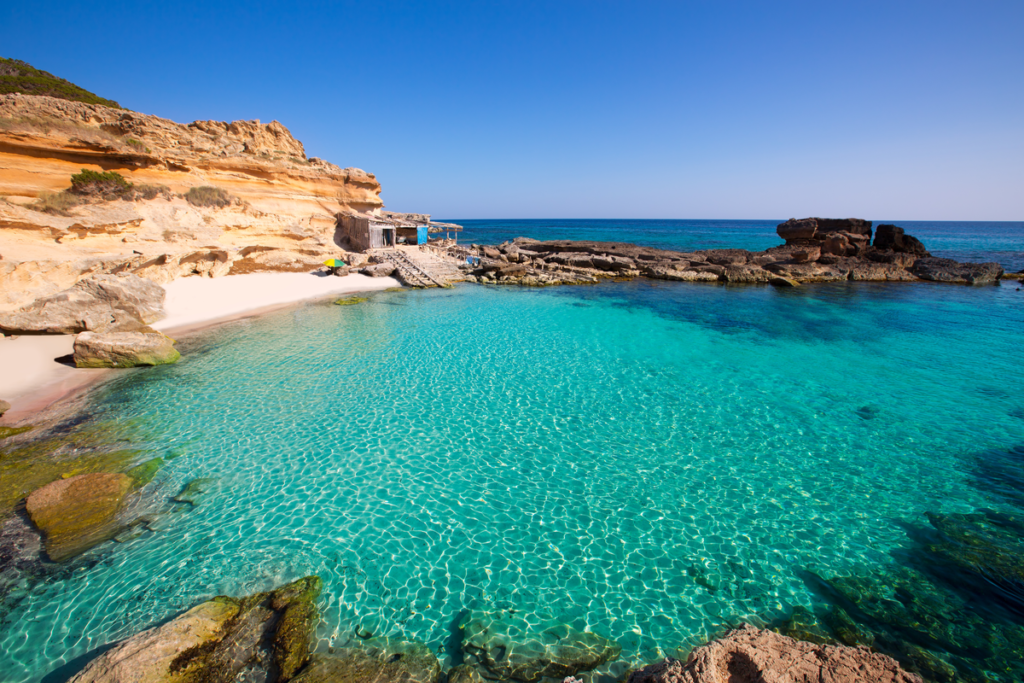 Rocks on the shore with turquoise waters, Formentera, Spain.