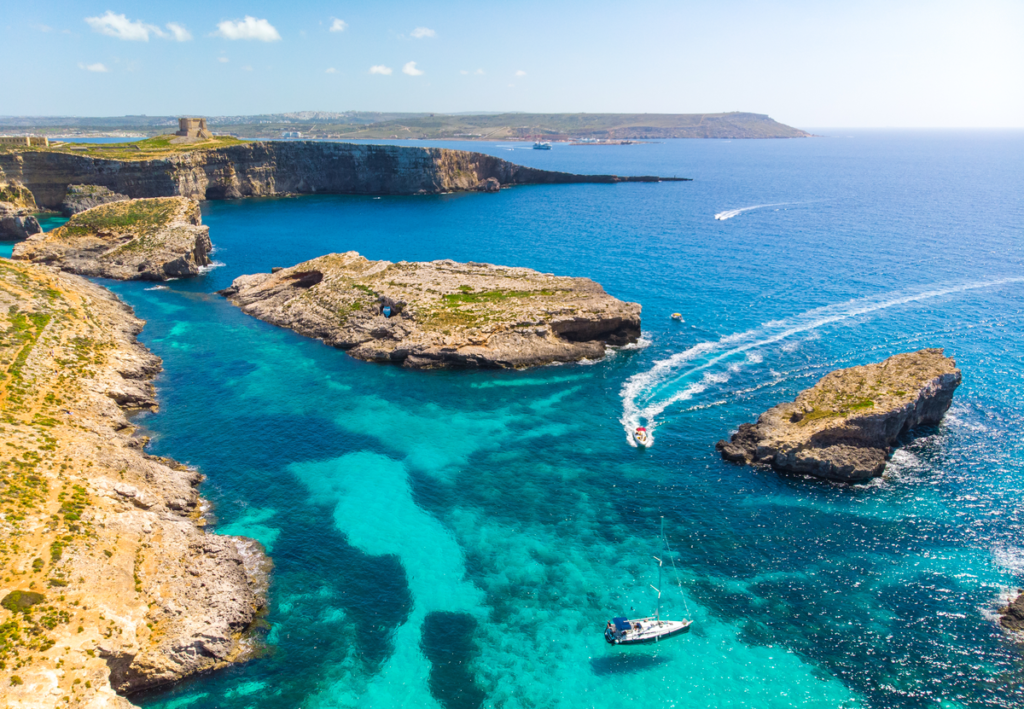 Aerial view of Comino island, Malta with boats in the water.