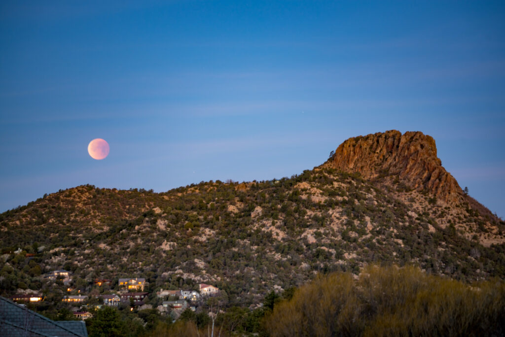 Blood Moon and Thumb Butte in Prescott, Arizona.  The moon is orange and sits next to the mountain.